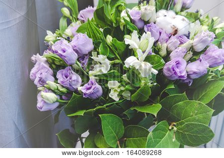 Rich bunch of violet spring garden flowers. Eustoma roses, green leaf. Fresh summer bouquet on nature background. Text Copy space, tonal curve