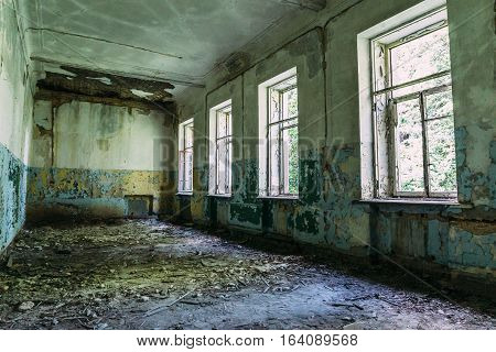 Abandoned small industrial building. room with windows, interior, devastation