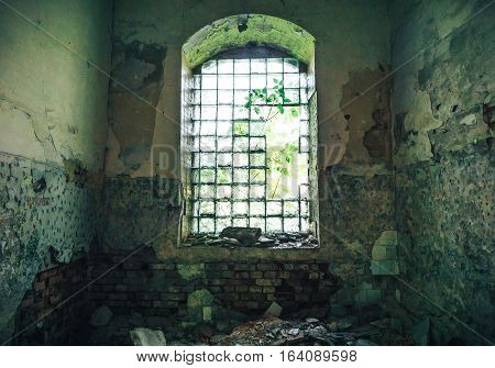 broken window in an old abandoned mansion with peeling walls