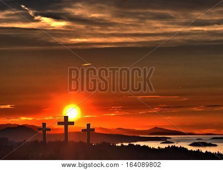 Three crosses, representing Jesus crucifixion, against a vibrant sunset sky, mountains and ocean.