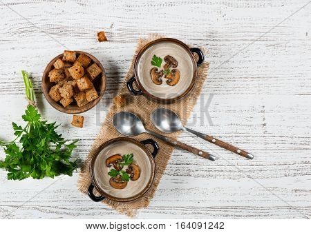 Top view of two bowls of portions of mushroom cream soup serving with croutons and parsley on a white rustic wooden table with copy space for text.