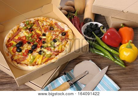 Freshly baked Pizza in a delivery box surrounded by various ingredients on a wood table