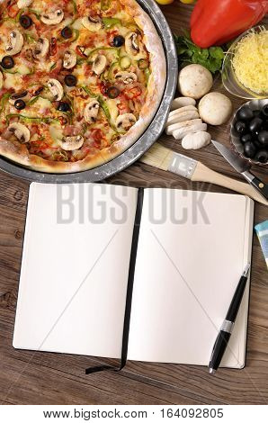Freshly baked Pizza with cookbook surrounded by various ingredients