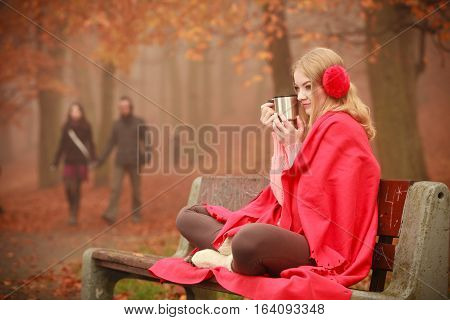 Autumn season time people concept. Young woman holding thermal mug. Cold weather outside. Lady has red clothing.