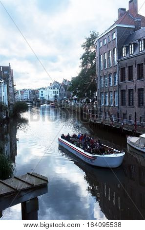London, UK - November 19, 2016:  Tourists view the city on a sightseeing boat in Ghent, Belgium