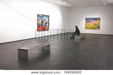 London, UK - November 17, 2016:  Art lover sits and views an artwork in a gallery in Ghent, Belgium