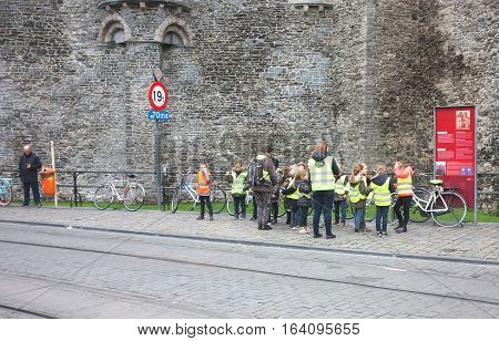 London, UK - November 17, 2016: School children in front of a castle wait for a transportation in Ghent, Belgium