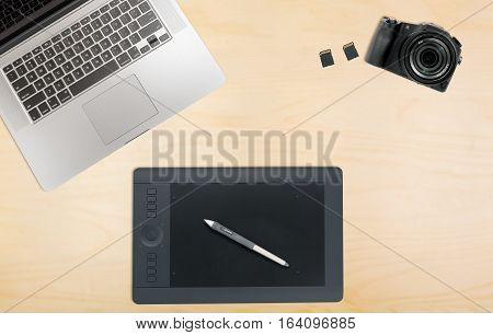 Photographers organized desk with laptop camera, memory cards and graphics tablet