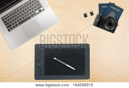 Photographers organized desk with laptop camera, memory cards and graphics tablet and passports