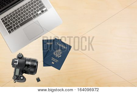 Photographers organized desk with laptop camera, memory cards and USA passports