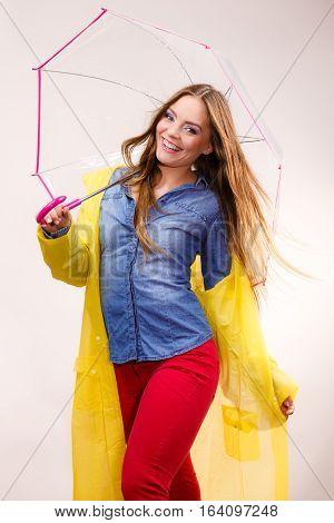 Woman rainy smiling girl wearing waterproof yellow coat standing under umbrella having fun. Meteorology forecasting and weather season concept