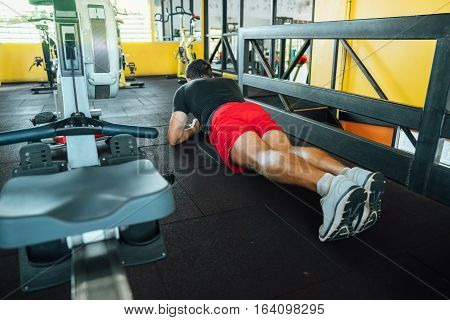 Young athlete doing exercise strap - Plank standing on his elbows at the gym. back view.