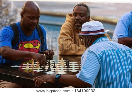 ATLANTA, GA - OCTOBER 2016:  African-American men play chess on a community chess table at Woodruff Park in downtown Atlanta in Atlanta GA on October 8 2016.