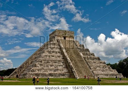 The Great Pyramid at Chichen Itza against blue skies with clouds.