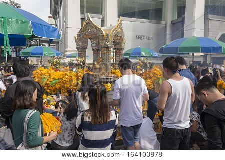 BANGKOKTHAILAND - DEC 31 : group of people pray at Erawan shrine in ratchaprasong area on december 31 2016 Thailand. there are many tourist worship at Erawan shrine in new year festival