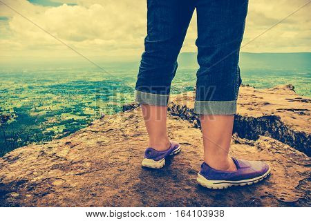 Closeup of tourist's feet on boulder at view point on summer day. Woman hiking accomplishment on the top of the mountain. Motivation and freedom concept. Cross process and vintage tone effect.