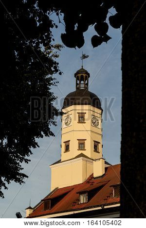 Nesvizh Belarus - September 09 2016: Nesvizh Town Hall - a monument of architecture of Belarus XVI-XVIII centuries. View on town hall framed by the silhouettes of branches and leaves of trees