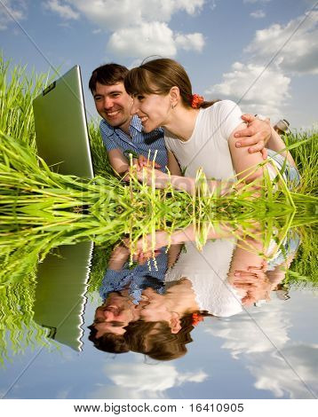 Casual happy couple on laptop computer outdoors. Lay on the green grass