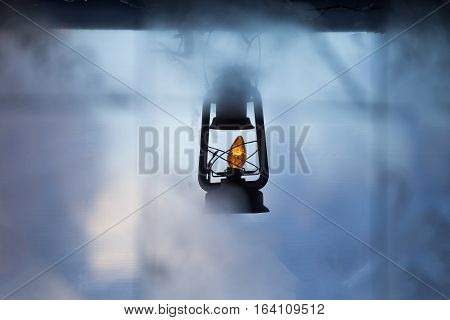Vintage hanging lantern with small light buld surrounded by fog