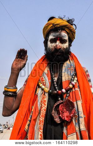 Allahabad Uttar Pradesh India- 15 January 2013: An Aghori Sadhu with long hairs ash and red color holy mark on face wearing human bones and rudraksha bead at Mahakumbh mela Allahabad Uttar Pradesh India. The Aghori are known to engage in post-mortem ritua