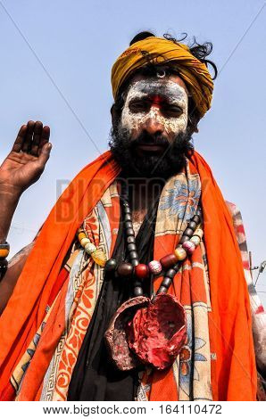Allahabad Uttar Pradesh India- 15 January 2013: An Aghori Sadhu with long hairs ash red color holy mark on face wearing human bones and rudraksha bead at Mahakumbh mela Allahabad Uttar Pradesh India. The Aghori are known to engage in post-mortem rituals.