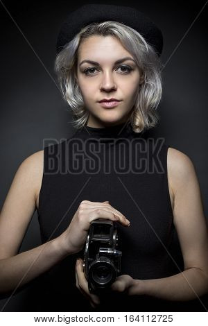 Woman holding a vintage video camera posing as a director filmmaker or cinematographer in the hollywood movie industry. The image depicts creative arts.