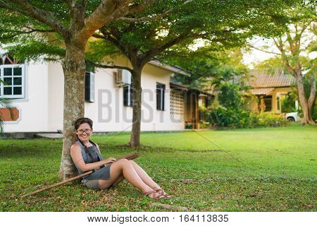 Girl with a broom in her hand on a clean green park lawn. Cleaning the leaves. Woman in the garden. Rest after work. Break. Happy janitor cleaner. sitting under a tree relaxing.