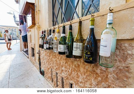 VERONA, ITALY- September 08 2016: The empty bottles of wine are hanging on the wall of Italian restaurant for the entourage on the street of Verona.