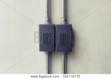 Close up of black lighting switch button on concrete wallpaper background with copy space.