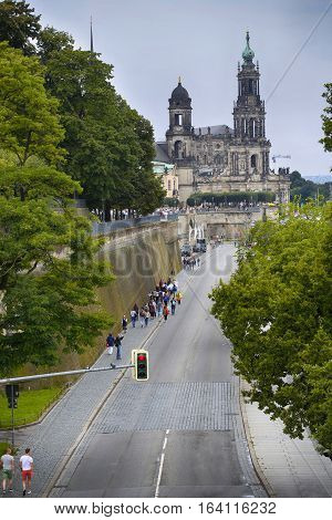 DRESDEN GERMANY - AUGUST 13 2016: Tourists walk and majestic view on Katholische Hofkirche from bridge Carolabrücke in Dresden State of Saxony Germany on August 13 2016.
