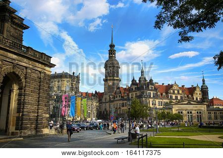 DRESDEN GERMANY - AUGUST 13 2016: Tourists walk on Theaterplatz street and majestic view on Saxony Dresden Castle (Residenzschloss) in Dresden State of Saxony Germany on August 13 2016.