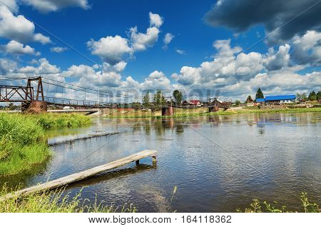 Summer landscape with an unusual bridge over the river Chusovaya. Russia. Ural