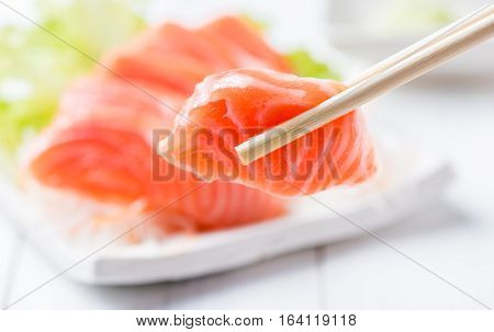 Salmon Sashimi Set With Chopsticks Holding A Piece Of Sliced Salmon
