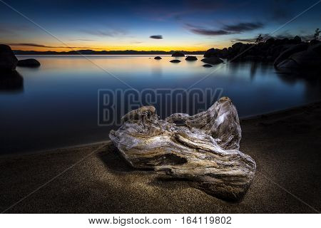 Driftwood On The Shore Of Lake Tahoe At Sunset. Wood Is Light Painted.