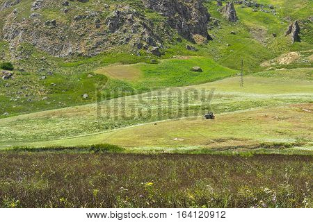 Tractor on the Wheat Fields on the Background of Sicilian Rocks