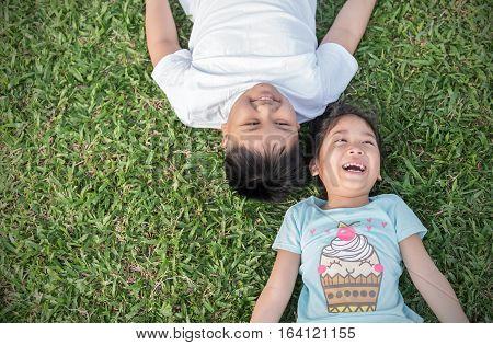 Smile Children Lie Down On Grass