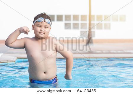 obese fat boy in swimming pool concept healthy and exercise