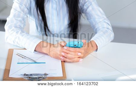 Woman working on celphone, sitting at the desk.