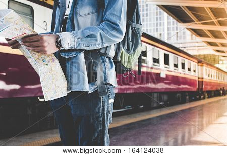 Backpacker Waiting For Long Journey Travel At Train Station With Backpack And Map On Hand. Travel Co