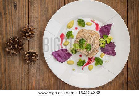 Pork medallions in cream sauce and micro greens on a white plate. Wooden background. Top view