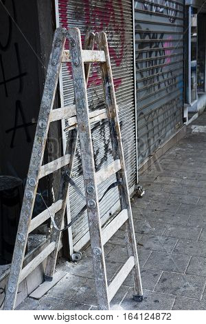 Foldable Wooden Ladder for Repairs of Shop in Tel Aviv. Splattered Ladder in the Street.