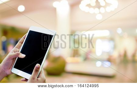 Hand hold and touch screen tablet,with abstract blur beautiful hotel lobby background concept idea.