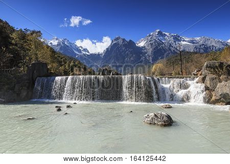 Waterfall on foreground and Jade Dragon Snow Mountain on background - Yunnan China