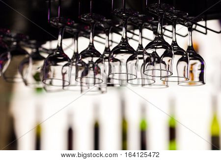 Glasses for fortified wine hang over a bar counter at restaurant against the background of the shelf with indistinct outlines of bottles.