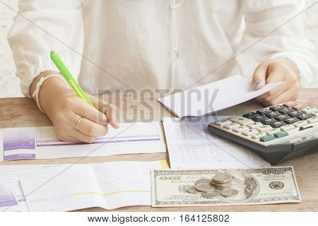 woman writing bill deposit with passbook bank for financial expense and income