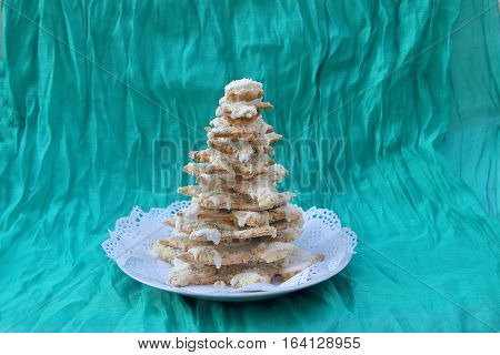 In the photo Christmas tree made of gingerbread sprinkled with melted white chocolate. The background is made of matter azure.