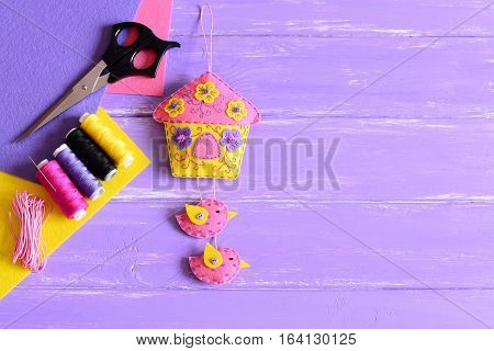 Creative wall decor for home. Handmade felt house with flowers and birds, sewing details set on a wooden background with empty place for text. How to decorate room wall with felt crafts. Top view
