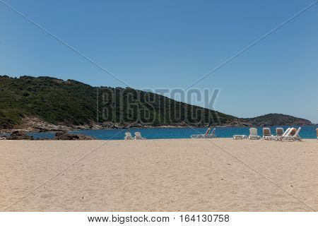 View Of The Blue Sea Paradisiac With The Beach Chairs And The Mountains Or Hills Behind