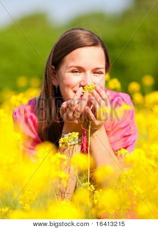 Pretty smiling girl relaxing on green meadow full of flowers. Soft focus. Focus on eyes. poster