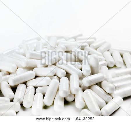 Pile of white capsules on white background. Close up high resolution product. Health care concept